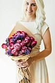 Junge Frau hält Strauß aus Rosen und Meerlavendel im Packpapier