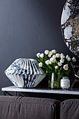 Console table with marble paper sculpture and bouquet of tulips, behind couch