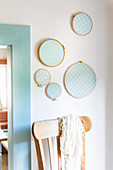 Arrangement of pale blue fabric mounted in embroidery frames on wall