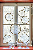 Lace doilies mounted in embroidery frames decorating window