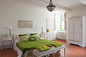 Green bedlinen and scatter cushions in vintage-style bedroom