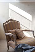 Striped scatter cushions on striped Baroque armchair in slanting sunshine