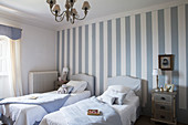 Twin beds in blue and white bedroom with striped accent wall