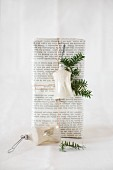 Vintage bell hung on gift wrapped in book pages