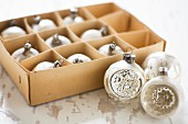 Vintage-style Christmas baubles in old cardboard box