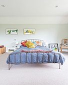 Colourful scatter cushions on metal bed against pale green bedroom wall