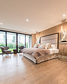 Glamorous bedroom in gold and beige with wooden floor