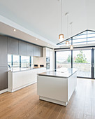 Open-plan kitchen island under open ceiling with glazed gable-end wall