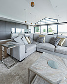 Patterned scatter cushions on grey sofa in large open-plan interior