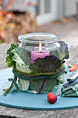 Preserving jar as a lantern clad with Brassica leaves
