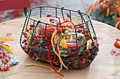 Wire basket with Malus (ornamental apple) and Rosa (rosehip)
