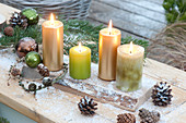 Simple candle decoration with 4 candles on wooden board, cones, Christmas tree balls