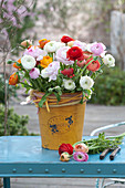 Lush bouquet with ranunculus (ranunculus) in a yellow bucket
