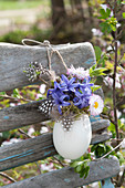 Small Easter bouquet in duck egg hung as a vase on chair back
