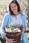 Woman bringing wicker basket as easter nest with easter eggs and easter bunny