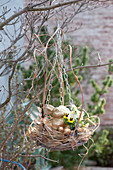 Basket bowl with grass as hanging Easter nest with easter bunny and easter eggs