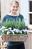 Woman bringing basket with Rosemary (Rosemary) and Viola