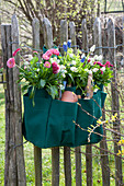 Gardener's bag misappropriated and planted hung on a fence