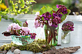 Small table decoration of flowers and bergenia (bergenie) leaves