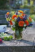 Colorful spring bouquet with geum, ajuga, alliaria