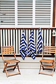 Hanging towels and two wooden folding chairs at the pool edge