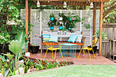 Pergola with wooden bench, metal chairs, table and hanging plant pots
