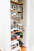 Shelves with storage jars and kitchen appliances in the pantry