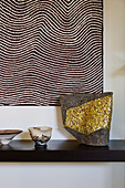 Sculpture with golden mosaic under a picture with wavy lines