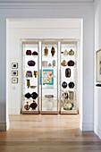 Drei moderne Glasvitrinen mit Vasen-Sammlung in einer Nische