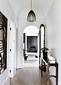 White hallway with antique console table and pendant lamp, open arched door to living room