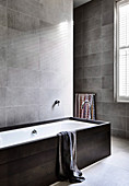 Bathtub in the bathroom with gray-tiled wall tiles