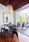 Schwarze Metallhocker um den Esstisch vor der Terrasse mit Sofa