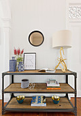 Industrial style shelf with decorative accessories and a table lamp