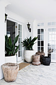 Large plant containers in the hallway with marble floors