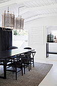 Table and chairs in the dining room with white wooden ceiling