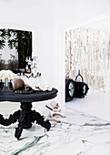 Antique wooden table with candle holder and decorative objects on marble floor, woolen wall hanging in the background