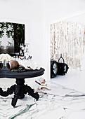 Antik-Holztisch mit Kerzenhalter und Dekoobjekten auf Marmorfussboden, im Hintergrund Wandbehang aus Wolle