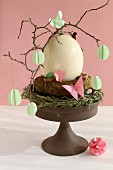 Twigs with paper decorations around ostrich egg on cake stand