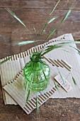 Gräser in einer grünen Vase auf abgerissenem Pappkarton