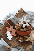 Clay Christmas decorations in white and terracotta on piece of bark