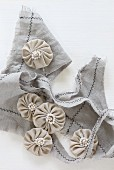 Small fabric rosettes with beads on piece of frayed fabric
