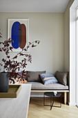 Blätterzweige auf dem Esstisch vor einer Holzbank mit Polster