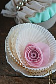 Pink fabric rose in stacked white paper cake cases