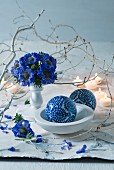 Posy of blue flowers next to white branch and ornamental spheres