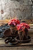 Kleine Sträuße aus Rosen und Nelken in zwei rostigen Metalltöpfchen