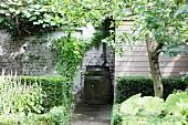 Old barrel used as water butt against garden wall in summery garden