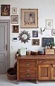 Alte Gemälde und Sonnenspiegel an der Wand über einer Kommode