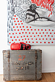 Red boxing gloves on old wooden trunk in front of modern artwork