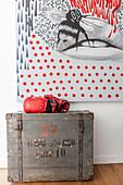 Rote Boxhandschuhe auf einer alten Holzkiste vor modernem Gemälde