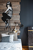 Graffito-style artwork painted on wooden boards on grey wall above bed